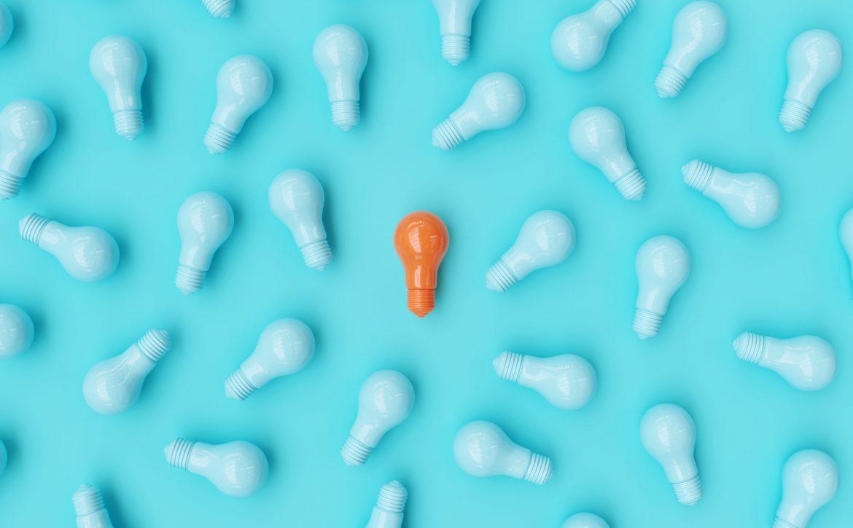 Orange,Light,Bulb,Among,Blue,Light,Bulbs,On,Blue,Background.